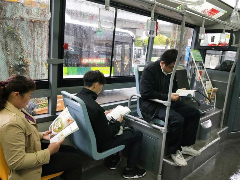 people reading books from library on bus