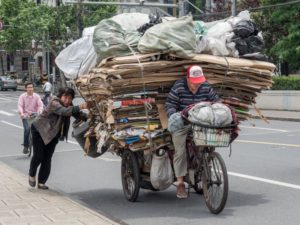 front view of man on tricycle recycling cardboard