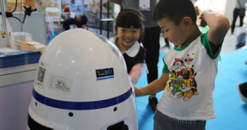 children playing with robot teacher at kindergarten in xinjiang