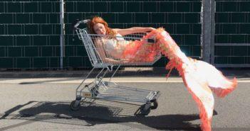 woman sitting in trolley wearing mermaid tail