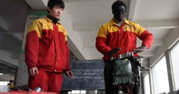 ghanaian mechanic working on car engine blindfolded