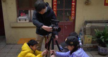 children helping man set up camera