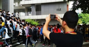 man taking picture as students enter gaokao in china