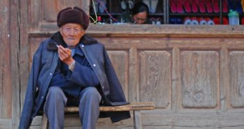 elderly man sitting on a bench and smoking in china