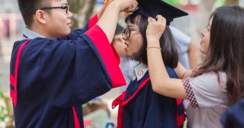 side view of two people helping girl put on graduation hat