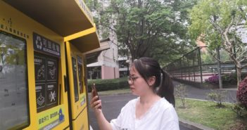 side view of student scanning QR code on campus rubbish sorting machine