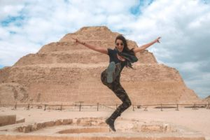 girl kicking air in front of pyramids in egypt