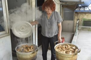 woman cooking zongzi in two pots