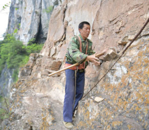 man with safety rope walking along cliff