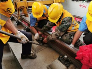 workers laying railway track in china