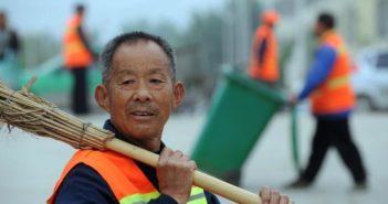 street cleaner holding broom over shoulder in china