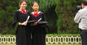man taking photo of two girls at graduation