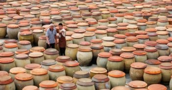father and son surrounded by large pots of soy sauce