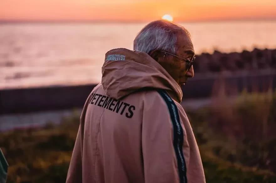 back and side view of elderly man posing for picture at sunset