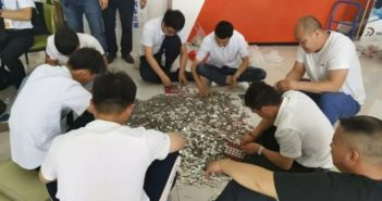 group of men sat in circle on floor counting coins