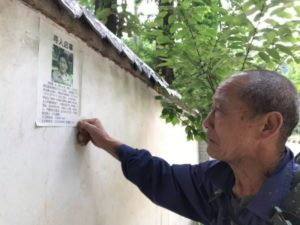 elderly man sticking missing poster on wall