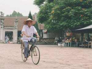 old man riding bike in village