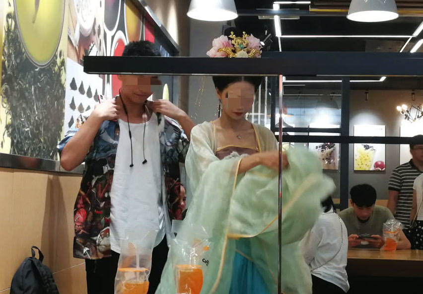 girl wearing traditional han dress with boy at drink store