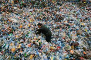 man in huge pile of plastic bottles