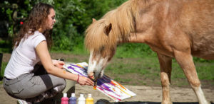 owner helping horse paint
