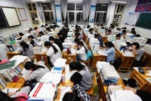 side view of students in classroom taking exam