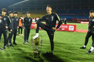 south korean football player putting foot on trophy