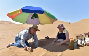 woman experiencing sand therapy in xinjiang desert