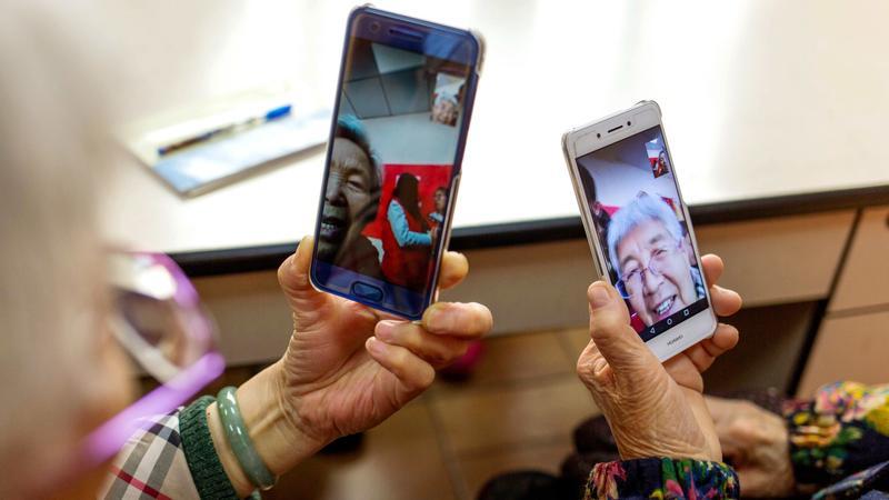two elderly people using smartphone