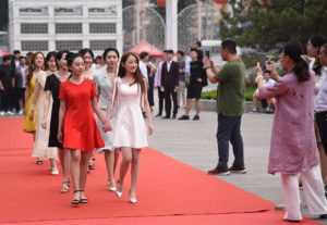 students walking down red carpet at university event