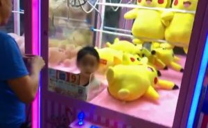 girl trapped in claw machine