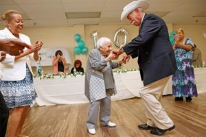 small elderly woman dancing with man