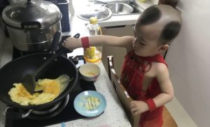 young boy cooking eggs at home
