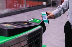 man scanning wechat QR code to enter station