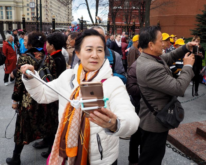 chinese tourists holding cameras in moscow