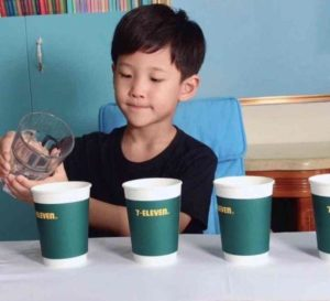 young boy pouring water into cups