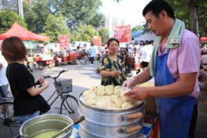 man cooking baozi on street in china