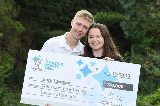 young couple posing for picture with giant cheque after winning lottery