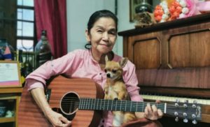 woman sitting in front of piano with guitar and dog