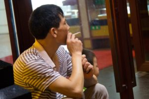 man sitting down and smoking next to child