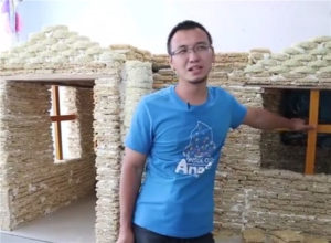 man posing in front of house made from instant noodles