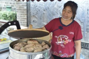 woman lifting lid to pot of roasted sweet potatoes