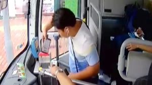 man putting mobile into money box on bus