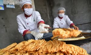 cooks making youtiao in china