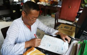teacher marking homework at rural school in china