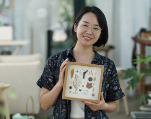 woman holding framed art made from plants