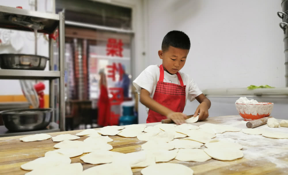 young boy making baozi skins