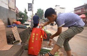 boy unpacking vegetables on the street