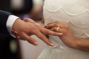 couple putting on wedding rings