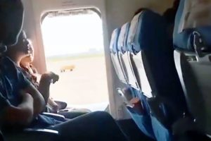 passengers sitting next to open emergency door on a plane