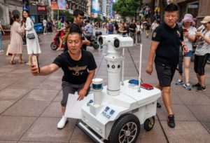 man taking picture with police robot in shanghai